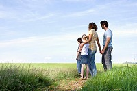 family standing on path in the countryside looking at the horizon