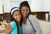 African mother and daughter hugging in kitchen
