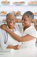 African small business owners hugging in bakery