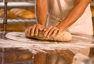 Man kneading dough at bakery