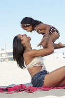 Mixed race mother holding daughter at beach