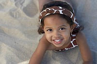 Young mixed race girl looking up at beach