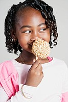 African girl eating candy apple