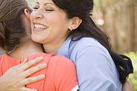 Hispanic mother hugging daughter (thumbnail)