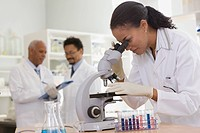 African scientist performing analysis in laboratory with microscope