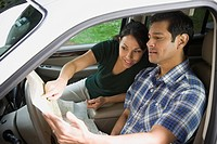 Hispanic couple looking at map in car
