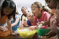 Children eating popcorn indoors