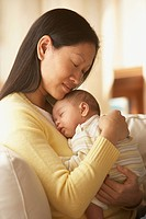 Asian mother and baby hugging with eyes closed