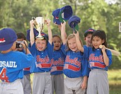 Children in baseball outfits cheering with trophy