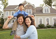 Portrait of Asian family in front of house
