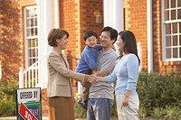 Asian family shaking hands with real estate agent