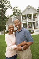 Portrait of senior African couple in front of house