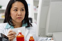 Asian female pharmacist working on computer