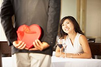 Asian woman smiling at man holding gift behind back