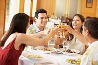 Hispanic couples toasting at restaurant