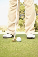 Close up of golfer putting on green