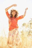 Hispanic woman dancing in sunlit field