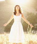 Hispanic woman standing with arms outstretched in sunlit field