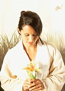 Hispanic woman in bathrobe holding flower