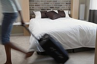 Blurred motion shot of woman pulling suitcase in bedroom
