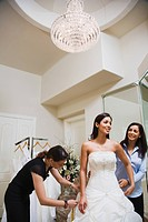 Hispanic woman being fitted for wedding dress