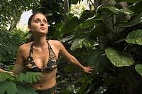 Hispanic woman wearing camouflage bikini in jungle