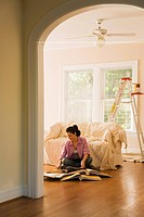 Hispanic woman looking at textile swatches in new home (thumbnail)