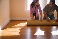 Hispanic couple unrolling carpet in new home