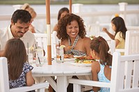 Hispanic family eating at outdoor restaurant