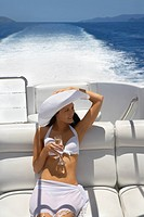 Pacific Islander woman drinking champagne on boat (thumbnail)