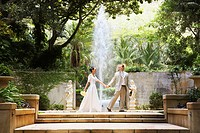 Bride and groom walking through jungle ruins