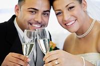 Multi_ethnic bride and groom toasting