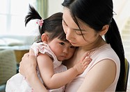 Asian mother hugging baby daughter