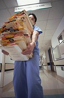 Hispanic male doctor carrying charts (thumbnail)