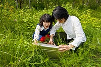 Asian couple opening briefcase in tall grass