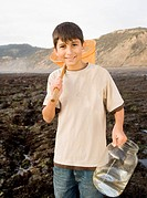 Hispanic boy holding net and jar at low tide