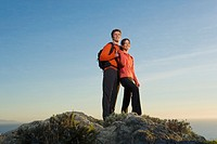 Hispanic couple hugging on mountain top