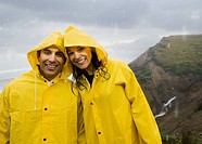 Hispanic couple in rain gear hugging