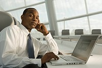 African businessman working on laptop and looking serious