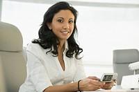 Hispanic businesswoman holding cell phone