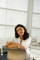 Hispanic businesswoman leaning on conference room chair