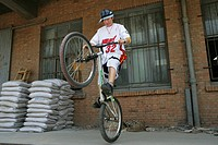 young man performing a stunt with a bicycle at 798 Art Zone,Beijing,China