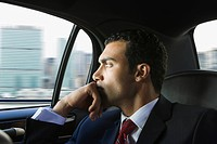 Serious Hispanic businessman riding in limousine