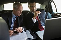 Businessmen using laptop in limousine (thumbnail)