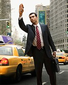 Hispanic businessman hailing taxi