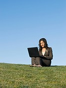 Mixed race businesswoman using laptop in grass
