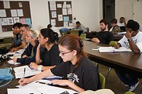 College students sitting at tables in classroom (thumbnail)