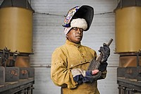 African American female welder posing with metal