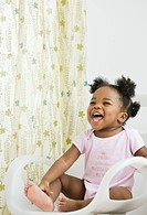 African American girl laughing in chair (thumbnail)