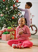 African American girl holding ornaments near Christmas tree